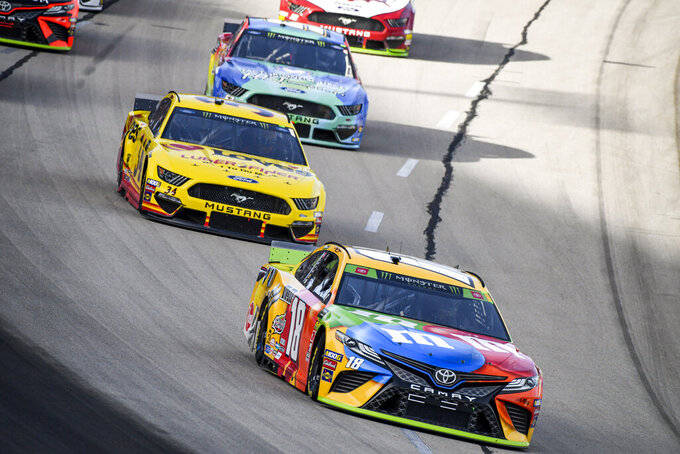 Kyle Busch (18) races into turn one during a NASCAR auto race at Texas Motor Speedway, Sunday, Nov. 3, 2019, in Fort Worth, Texas. (AP Photo/Larry Papke)