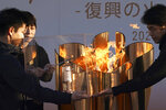 Officials light a lantern from the Olympic Flame at the end of a flame display ceremony in Iwaki, northern Japan, Wednesday, March 25, 2020. IOC President Thomas Bach has agreed