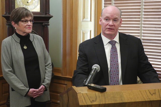Newly appointed Kansas Supreme Court Justice K.J. Wall, right, speaks to reporters as Gov. Laura Kelly watches during a news conference, Wednesday, March 11, 2020, at the Statehouse in Topeka, Kan. Wall is a 49-year-old Lawrence, Kan., attorney who formerly worked for the high court. (AP Photo/John Hanna)