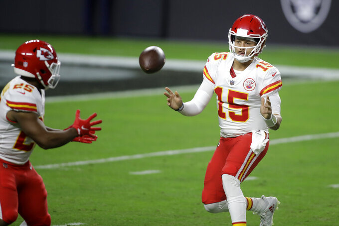 Kansas City Chiefs quarterback Patrick Mahomes (15) tosses the ball to running back Clyde Edwards-Helaire (25) during the first half of an NFL football game against the Las Vegas Raiders, Sunday, Nov. 22, 2020, in Las Vegas. (AP Photo/Isaac Brekken)
