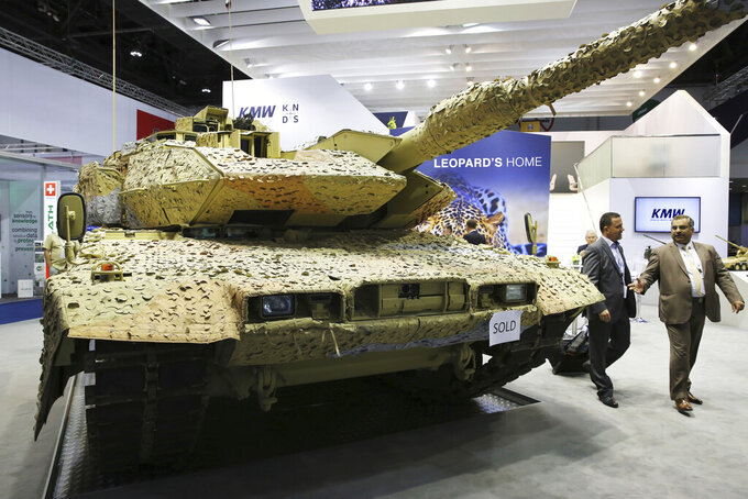 """FILE - In this Feb. 22, 2017 file photo, men walk past a Krauss-Maffei Wegmann Leopard tank with a """"sold"""" sign on it at the International Defense Exhibition and Conference, known by the acronym IDEX, in Abu Dhabi, United Arab Emirates. Israel has decided not to send a delegation of defense companies to the 2021 IDEX arms fair in the United Arab Emirates next week. Officials on Monday, Feb. 15, 2021, cited coronavirus restrictions that have forced the closure of Israel's international airport. Dozens of Israeli companies, including state-owned Israel Aerospace Industries and Rafael Advanced Defense Systems, had planned on sending delegations. (AP Photo/Jon Gambrell, File)"""