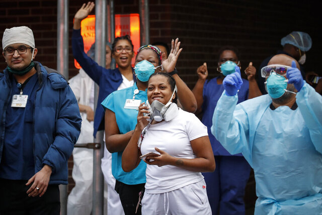Medical workers cheer and acknowledge pedestrians and FDNY firefighters who gathered to applaud them at 7 p.m. outside Brooklyn Hospital Center, Tuesday, April 14, 2020, in New York. (AP Photo/John Minchillo)