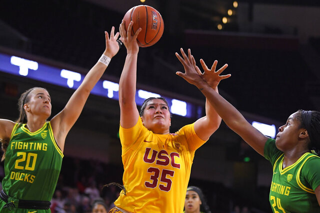 Southern California forward Alissa Pili, center, shoots as Oregon guard Sabrina Ionescu, left, and forward Ruthy Hebard defend during the first half of an NCAA women's college basketball game Sunday, Feb. 16, 2020, in Los Angeles. (AP Photo/Mark J. Terrill)