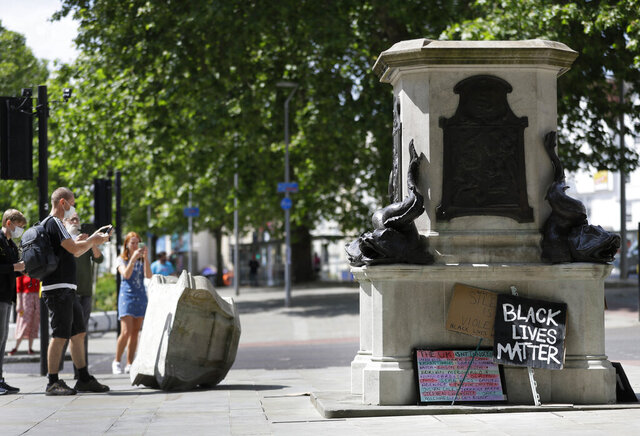 FILE - In this file photo dated Monday, June 8, 2020, people look at the empty pedestal after a statue of notorious slave trader Edward Colston was pulled down during a Black Lives Matter demo, in Bristol, England.     Four people have been were charged with criminal damage over the toppling of the 17th-century slave trader  Colston statue, according to an announcement Wednesday Dec. 9, 2020, by Britain's Crown Prosecution Service.  (AP Photo/Kirsty Wigglesworth, FILE)