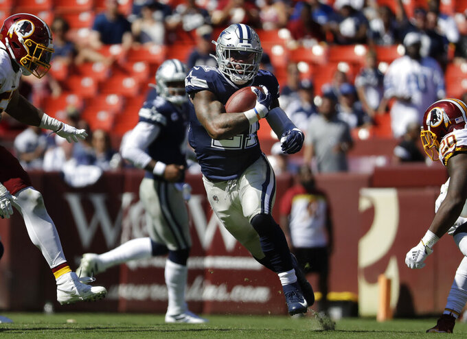 Dallas Cowboys running back Ezekiel Elliott (21) runs past members of the Washington Redskins in the second half of an NFL football game, Sunday, Sept. 15, 2019, in Landover, Md. (AP Photo/Evan Vucci)