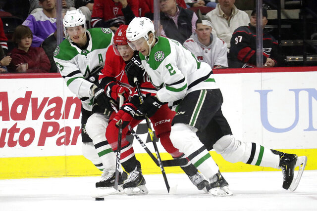Dallas Stars' John Klingberg (3) and Jamie Oleksiak (2) battle Carolina Hurricanes' Ryan Dzingel (18) for the puck during the third period of an NHL hockey game against the Carolina Hurricanes in Raleigh, N.C., on Tuesday, Feb. 25, 2020. (AP Photo/Chris Seward)