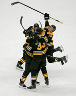 Boston Bruins players crowd around Patrice Bergeron after he scored the winning goal late during the third period of an NHL hockey game against the Florida Panthers, Thursday, March 7, 2019, in Boston. (AP Photo/Mary Schwalm)