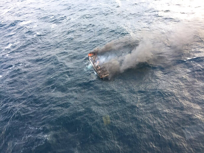 This photo provided by the Korea Jeju Coast Guard, shows a fishing boat in a smoke in waters near the southern island of Jeju, in South Korea, Tuesday, Nov. 19, 2019. South Korea's coast guard says about a dozen people are missing from a fishing boat that caught fire in waters near the southern island of Jeju. (Korea Jeju Coast Guard via AP)