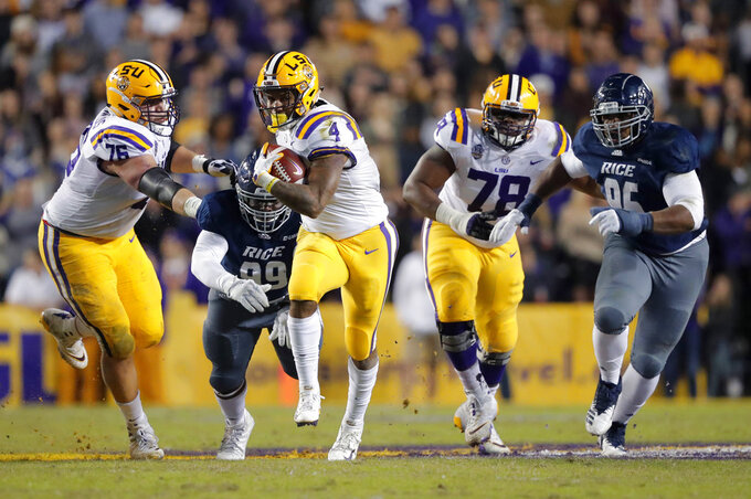 LSU running back Nick Brossette (4) carries past Rice defensive lineman Myles Adams (99) and defensive tackle Roe Wilkins (95) in the first half of an NCAA college football game in Baton Rouge, La., Saturday, Nov. 17, 2018. (AP Photo/Gerald Herbert)