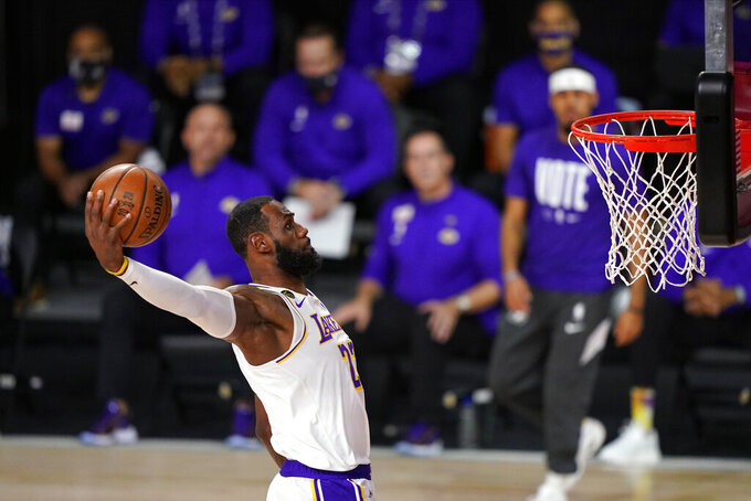 FILE - In this Oct. 11, 2020, file photo, Los Angeles Lakers' LeBron James dunks during the first half in Game 6 of basketball's NBA Finals against the Miami Heat in Lake Buena Vista, Fla.  James was announced Saturday, Dec. 26,  as the winner of The Associated Press' Male Athlete of the Year award for a record-tying fourth time. (AP Photo/Mark J. Terrill, File)