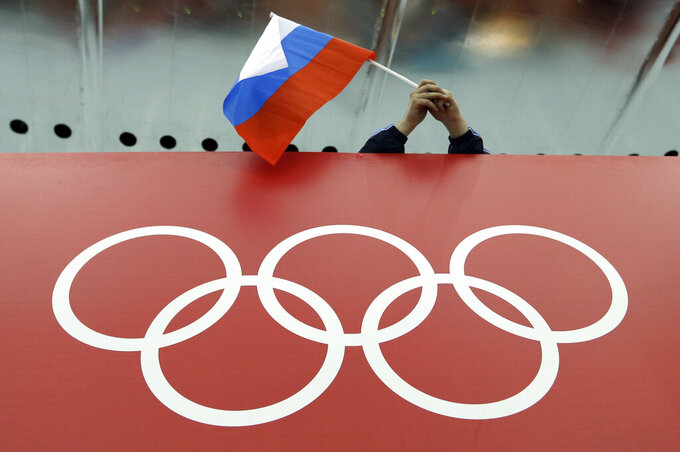 FILE - In this Feb. 18, 2014, file photo, a Russian skating fan holds the country's national flag over the Olympic rings before the start of the men's 10,000-meter speedskating race at Adler Arena Skating Center during the 2014 Winter Olympics in Sochi, Russia. The World Anti-Doping Agency banned Russia on Monday Dec. 9, 2019 from the Olympics and other major sporting events for four years, though many athletes will likely be allowed to compete as neutral athletes. (AP Photo/David J. Phillip, File)