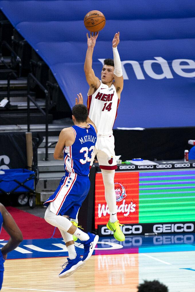 Miami Heat's Tyler Herro, right, releases a 3-point shot over Philadelphia 76ers' Dakota Mathias, left, during overtime of an NBA basketball game Tuesday, Jan. 12, 2021, in Philadelphia. (AP Photo/Chris Szagola)