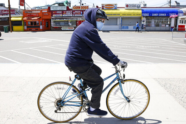 A man wearing a protective mask and gloves cycles past the Boardwalk across from the Hampton Beach State Park in Hampton, N.H., Tuesday, May 19, 2020. Beaches in New Hampshire have been closed since March by state order due to the COVID-19 virus outbreak. (AP Photo/Charles Krupa)