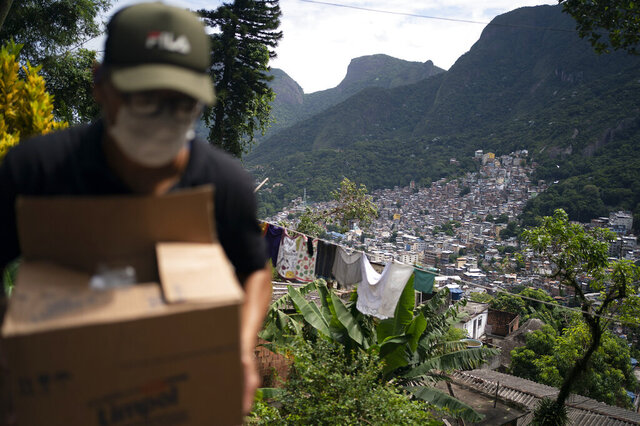 A local volunteer carries a package with soap and detergent to be distributed in an effort to stop the spread of the new coronavirus in the Rocinha slum of Rio de Janeiro, Brazil, Tuesday, March 24, 2020. (AP Photo/Leo Correa)
