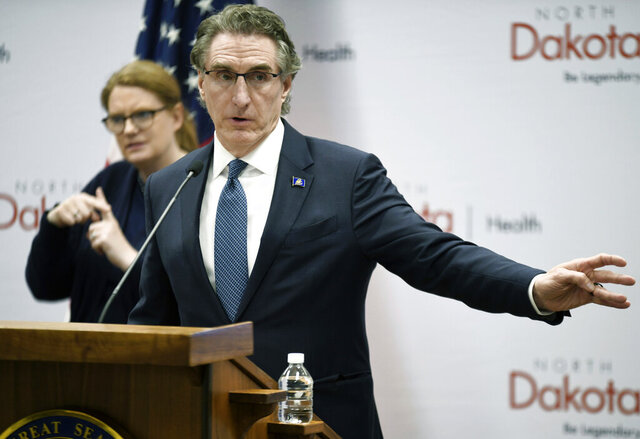 In this March 27, 2020 file photo North Dakota Gov. Doug Burgum speaks during a news conference at the state Capitol in Bismarck, N.D. Burgum said a major presidential disaster declaration has been approved as the number of COVID-19 cases in North Dakota continues to rise. Burgum also extended closures Wednesday, April1, 2020 for many businesses by two weeks, until April 20. (Mike McCleary/The Bismarck Tribune via AP)