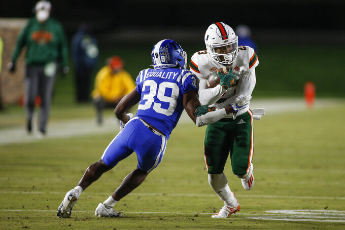 Miami running back Cam'Ron Harris (23) carries the ball as Duke cornerback Jeremiah Lewis (39) tries to make the tackle during the first half of an NCAA college football game Saturday, Dec. 5, 2020, in Durham, N.C. (Nell Redmond/Pool Photo via AP)
