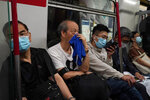 A passenger covers his nose and mouth with a towel to help protect himself against the coronavirus in a subway car in Hong Kong, Friday, Oct. 16, 2020. (AP Photo/Kin Cheung)
