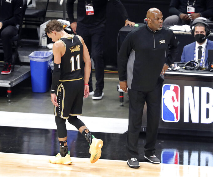 """FILE- In this July 3, 2021, file photo, with 39 seconds remaining interim head coach Nate McMillan pulls his players, last but not least Trae Young, as the Atlanta Hawks season comes to an end falling to the Milwaukee Bucks in Game 6 of the NBA Eastern Conference Finals in Atlanta. As the World Series comes to Atlanta for the first time since 1999, there is hope that the city — once immortalized by Sports Illustrated as """"Loserville"""" — and the entire state of Georgia, for that matter, could be taking a turn toward some long-overdue parades and celebrations.  (Curtis Compton/Atlanta Journal-Constitution via AP, File)"""