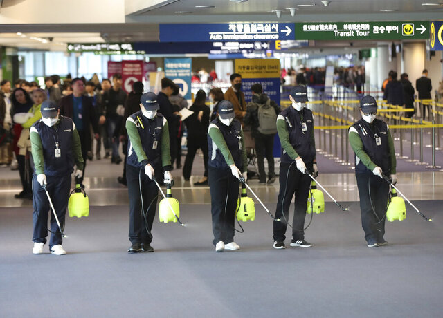Workers spray antiseptic solution in the arrival lobby amid rising public concerns over the possible spread of a new coronavirus at Incheon International Airport in Incheon, South Korea, Tuesday, Jan. 21, 2020. Heightened precautions were being taken in China and elsewhere Tuesday as governments strove to control the outbreak of a novel coronavirus that threatens to grow during the Lunar New Year travel rush. (Suh Myung-geon/Yonhap via AP)