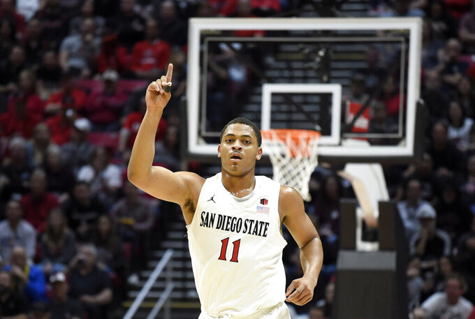 FILE - In this Feb. 25, 2020 file photo, San Diego State forward Matt Mitchell (11) points skyward during the first half of an NCAA college basketball game against Colorado State in San Diego. San Diego State was three days away from finding out whether it would be a No. 1 or 2 seed in the NCAA Tournament when March Madness was canceled because of the coronavirus pandemic. Their season ended before they could find out how truly historic it could have been. They finished 30-2, ranked No. 6 and with a Mountain West Conference regular-season championship banner hanging in Viejas Arena. (AP Photo/Denis Poroy, File)