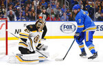 Boston Bruins goalie Tuukka Rask, left, of Finland, makes a save against St. Louis Blues' Patrick Maroon during the second period of an NHL hockey game Saturday, Feb. 23, 2019, in St. Louis. (AP Photo/Dilip Vishwanat)