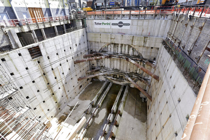 FILE - In this April 3, 2017, file photo, a concrete-walled pit surrounds a circular, five-foot deep concrete wall where a massive tunnel machine was expected to break through the next day as it completes boring for the State Route 99 highway in Seattle. On Friday, Dec. 13, 2019, a jury awarded the Washington State Department of Transportation $57.2 million in damages over delays in the construction of the tunnel. (AP Photo/Elaine Thompson, File)