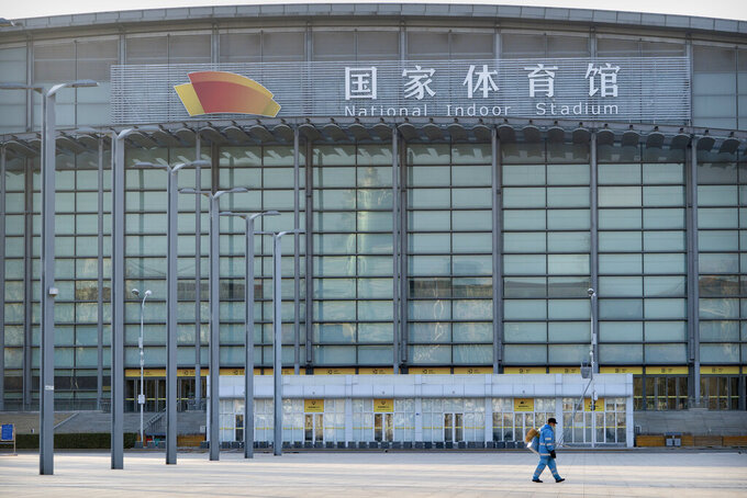 """A maintenance worker walks past the National Indoor Stadium, which will again be a venue for the 2022 Beijing Winter Olympics, in Beijing, Tuesday, Feb. 2, 2021. The 2022 Beijing Winter Olympics will open a year from now. Most of the venues have been completed as the Chinese capital becomes the first city to hold both the Winter and Summer Olympics. Beijing held the 2008 Summer Olympics. But these Olympics are presenting some major problems. They are already scarred by accusations of rights abuses including """"genocide""""against more than 1 million Uighurs and other Muslim ethnic groups in western China. (AP Photo/Mark Schiefelbein)"""