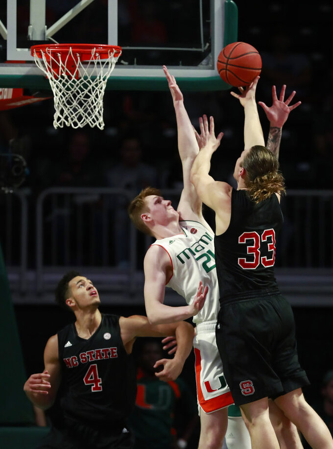 North Carolina State forward Wyatt Walker (33) goes up for a shot against Miami forward Sam Waardenburg (21) during the first half of an NCAA college basketball game, Thursday, Jan. 3, 2019, in Coral Gables, Fla. North Carolina State defeated Miami 87-82. (AP Photo/Wilfredo Lee)