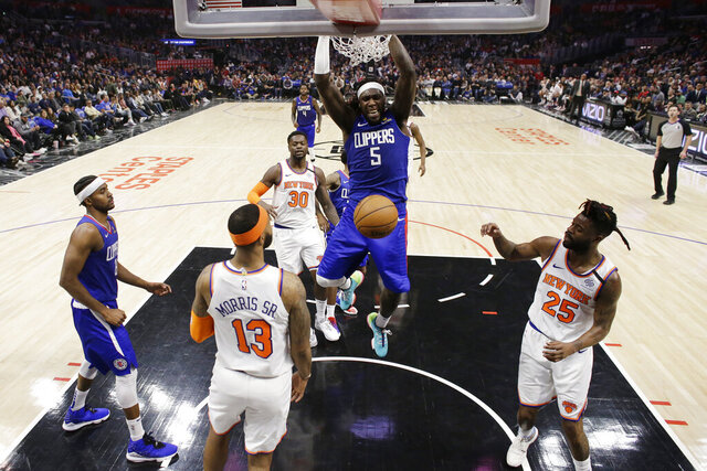 Los Angeles Clippers' Montrezl Harrell (5) dunks over New York Knicks' Marcus Morris Sr. (13) and Reggie Bullock (25) during the second half of an NBA basketball game Sunday, Jan. 5, 2020, in Los Angeles. (AP Photo/Marcio Jose Sanchez)