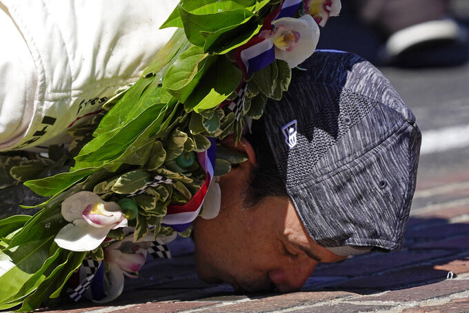 Helio Castroneves, of Brazil, kisses the yard of bricks at the start/finish line as he celebrates after winning after winning the Indianapolis 500 auto race at Indianapolis Motor Speedway, Sunday, May 30, 2021, in Indianapolis. (AP Photo/Paul Sancya)