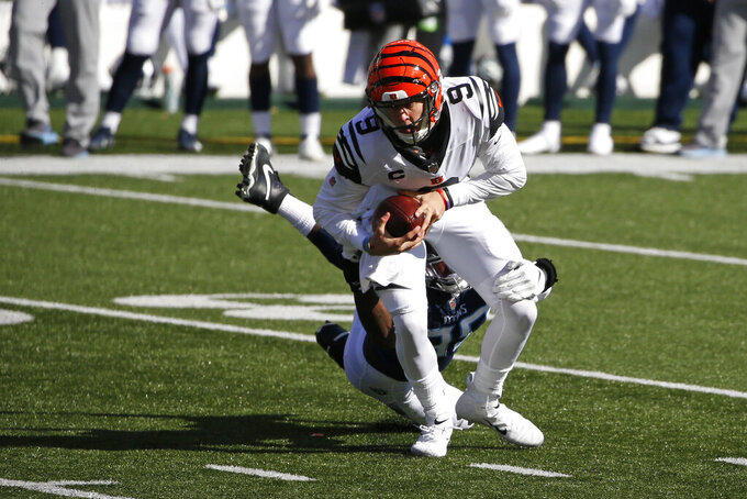 Cincinnati Bengals quarterback Joe Burrow (9) runs out of the tackle of Tennessee Titans' Jadeveon Clowney (99) during the first half of an NFL football game, Sunday, Nov. 1, 2020, in Cincinnati. (AP Photo/Gary Landers)