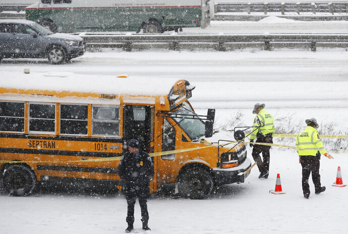 FILE - In this Feb. 5, 2019, file photo, law enforcement personnel investigate a scene where a school bus driver was shot along Interstate 35W and 94 near downtown Minneapolis. Kenneth Lilly who shot and wounded school bus driver Thomas Benson on a Minneapolis freeway during a snowstorm has been sentenced to more than seven years in prison. Lilly was convicted for the February attack that left Benson deaf in one ear and unable to continue working as a bus driver due to nerve damage in his hand. (Richard Tsong-Taatarii/Star Tribune via AP, File)