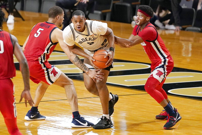 Vanderbilt's D.J. Harvey, center, is defended by Mississippi's KJ Buffen (5) and Devontae Shuler, right, in the first half of an NCAA college basketball game Saturday, Feb. 27, 2021, in Nashville, Tenn. (AP Photo/Mark Humphrey)