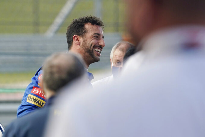 McLaren driver Daniel Ricciardo, of Australia, smiles after driving the late  NASCAR driver Dale Earnhardt's iconic 1984 No. 3 Wrangler Chevrolet Monte Carlo before an open practice for the Formula One U.S. Grand Prix auto race at the Circuit of the Americas, Saturday, Oct. 23, 2021, in Austin, Texas. Ricciardo was allowed to drive the car as a reward from his McLaren boss, Zak Brown, for winning his first race with the team. (AP Photo/Eric Gay)