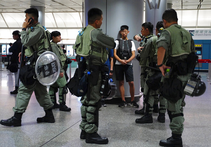 Riot police check a passenger's bag at the airport express station in downtown Hong Kong, Saturday, Sept. 7, 2019. Hong Kong authorities were limiting airport transport services and controlling access to terminals Saturday as they braced for a second weekend of disruption following overnight demonstrations that turned violent. (AP Photo/Vincent Yu)