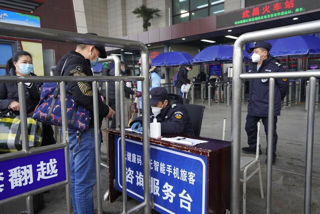 Travelers are screened before entering the Wuchang train station at the start of the annual Lunar New Year travel in Wuhan in central China's Hubei province on Thursday, Jan. 28, 2021. Efforts to dissuade Chinese from traveling for Lunar New Year appeared to be working as Beijing's main train station was largely quiet and estimates of passenger totals were smaller than in past years.  (AP Photo/Ng Han Guan)