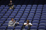 A few fans sit in a mostly empty Greensboro Coliseum after the NCAA college basketball games were cancelled at the Atlantic Coast Conference tournament in Greensboro, N.C., Thursday, March 12, 2020. The biggest conferences in college sports all canceled their basketball tournaments because of the new coronavirus, seemingly putting the NCAA Tournament in doubt.(AP Photo/Gerry Broome)