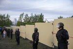 Police officers stand in front of a new built fence during a protest against plans to construct a cathedral in a park in Yekaterinburg, Russia, Wednesday, May 15, 2019. Hundreds of riot police have surrounded a park in Russia's fourth-largest city before what's expected to be a third consecutive day of protests against building a new cathedral. (AP Photo/Anton Basanayev)
