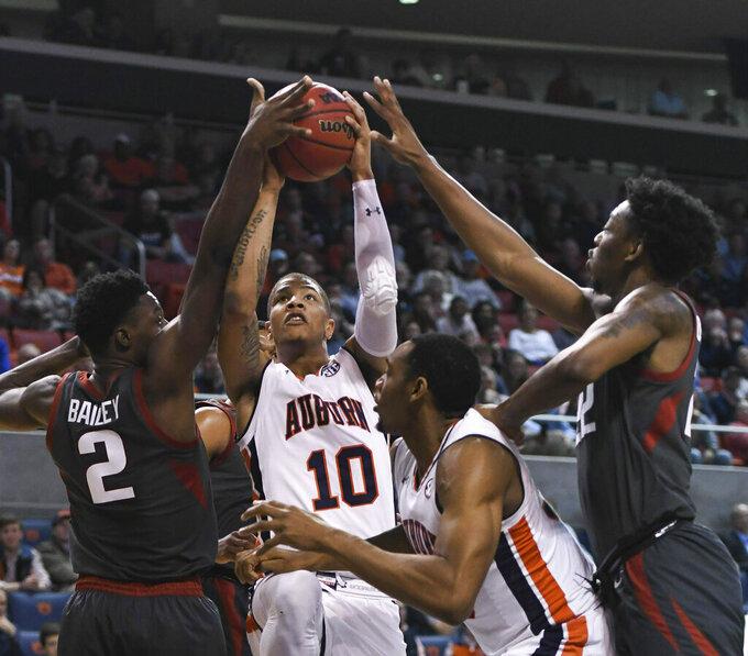 Arkansas forward Adrio Bailey (2) fouls Auburn guard Samir Doughty (10) during the first half of an NCAA college basketball game Wednesday, Feb. 20, 2019, in Auburn, Ala. (AP Photo/Julie Bennett)