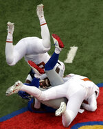 Texas defensive back B.J. Foster, top, dives over teammate Caden Sterns (7) while tackling Kansas wide receiver Daylon Charlot, bottom, during the second half of an NCAA college football game in Lawrence, Kan., Friday, Nov. 23, 2018. Texas defeated Kansas 24-17. (AP Photo/Orlin Wagner)