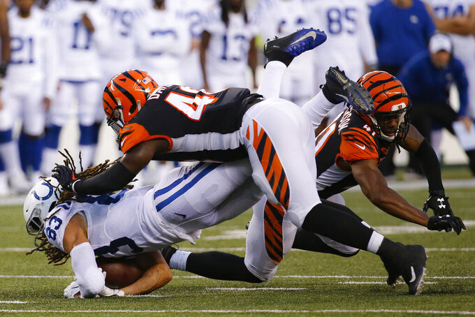 Indianapolis Colts wide receiver Krishawn Hogan (83) is tackled by Cincinnati Bengals linebacker Deshaun Davis, center, and defensive back Trayvon Henderson (41) during the first half of an NFL preseason football game Thursday, Aug. 29, 2019, in Cincinnati. (AP Photo/Frank Victores)
