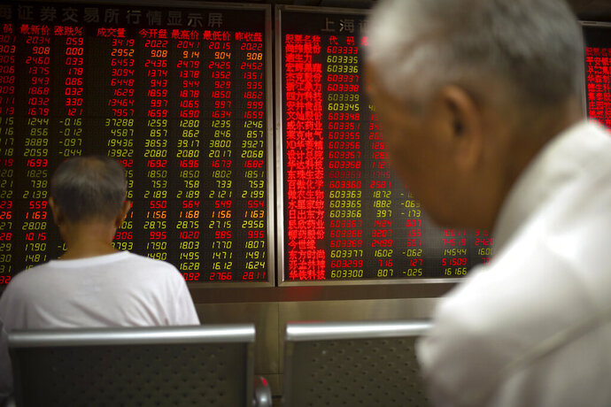 Chinese investors monitor stock prices at a brokerage house in Beijing, Thursday, June 20, 2019. Asian shares were higher on Thursday, with the Shanghai benchmark up 2.6%, after the Federal Reserve reaffirmed that it's prepared to cut interest rates if needed to shield the U.S. economy from trade conflicts or other threats. (AP Photo/Mark Schiefelbein)