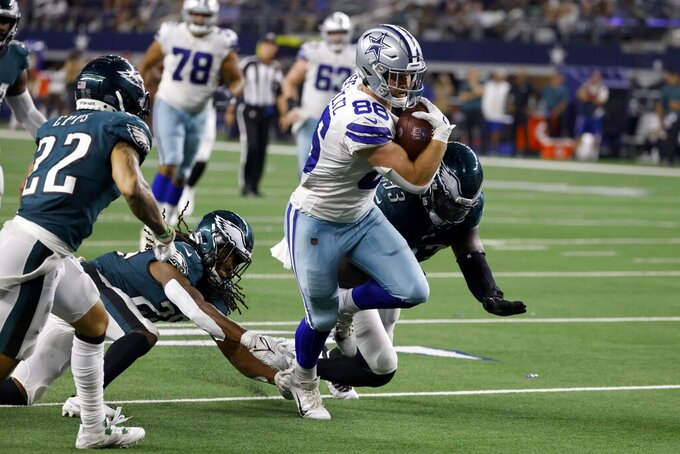 Dallas Cowboys tight end Dalton Schultz (86) breaks tackle attempts by Philadelphia Eagles' Milton Williams (93) and others as he sprints to the end zone for a touchdown in the second half of an NFL football game in Arlington, Texas, Monday, Sept. 27, 2021. (AP Photo/Ron Jenkins)