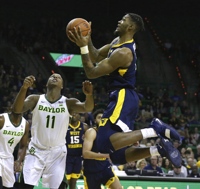 West Virginia forward Derek Culver, right, shoots over Baylor guard Mark Vital, left, in the first half of an NCAA college basketball game, Saturday, Feb. 23, 2019, in Waco, Texas. (Rod Aydelotte/Waco Tribune-Herald via AP)