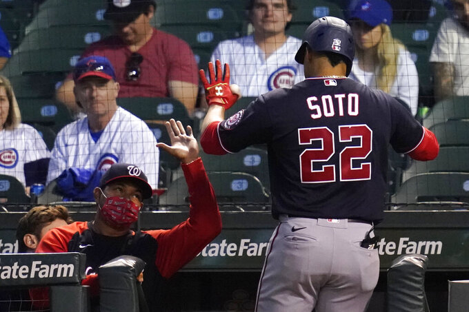 Washington Nationals manager Dave Martinez, left, congratulates Juan Soto after Juan Soto hit a solo home run during the fifth inning of a baseball game against the Chicago Cubs in Chicago, Wednesday, May 19, 2021. (AP Photo/Nam Y. Huh)