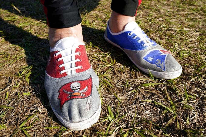 A fan arrives wearing shoes from both Tampa Bay Buccaneers quarterback Tom Brady's teams before the NFL Super Bowl 55 football game between the Kansas City Chiefs and Tampa Bay Buccaneers, Sunday, Feb. 7, 2021, in Tampa, Fla. (AP Photo/Mark Humphrey)