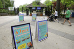Visitors to the Franklin Park Zoo walk past the signs advising safe distancing near an entrance to the zoo, Thursday, May 28, 2020, in Boston. The zoo was open to members only Thursday for the first time in about two months due to concerns about COVID-19. Safety measures such as one way paths and safe distancing have been implemented at the zoo. The zoo is to open to the general public starting June 4. (AP Photo/Steven Senne)
