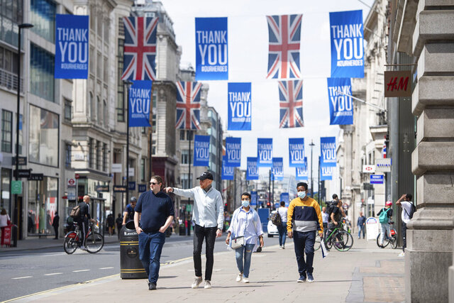 People walk on Oxford Street, in London, Wednesday June 17, 2020, as further coronavirus lockdown restrictions are lifted in England. (Dominic Lipinski/PA via AP)
