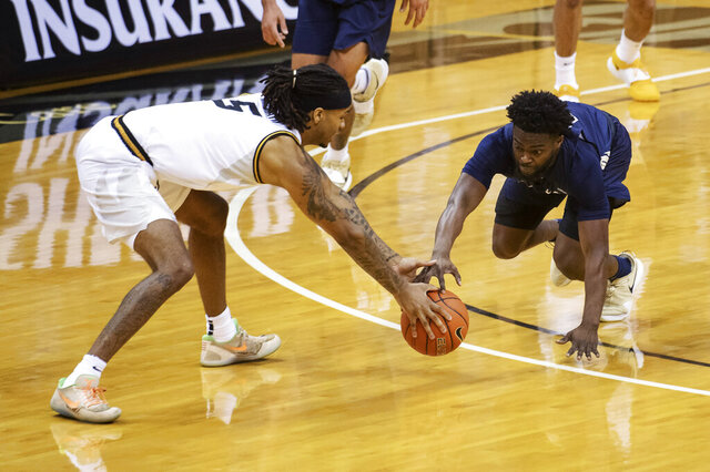 Missouri's Mitchell Smith, left, and Oral Roberts' RJ Glasper scramble for a loose ball during the first half of an NCAA college basketball game Wednesday, Nov. 25, 2020, in Columbia, Mo. (AP Photo/L.G. Patterson)