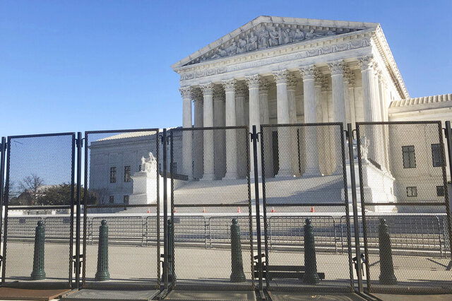 Anti-scaling fencing has been placed in front of the Supreme Court, which stands across the street from the U.S. Capitol, Sunday, Jan. 10, 2021, in Washington. (AP Photo/Alan Fram)
